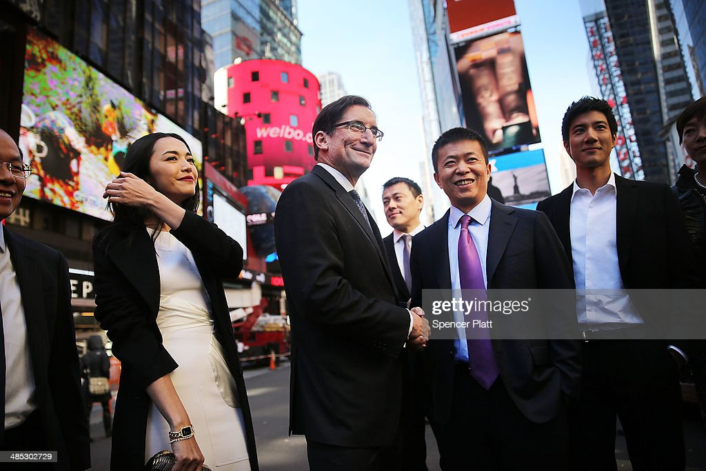 China's Weibo CEO Charles Chao (center right) stands with Robert Greifeld, Nasdaq CEO, moments after Weibo began trading on the Nasdaq exchange under the ticker symbol WB on April 17, 2014 in New York City. Weibo Corp, a Twitter-like messaging service company, priced its initial public offering (IPO) at $17 per American Depository Share (ADS).