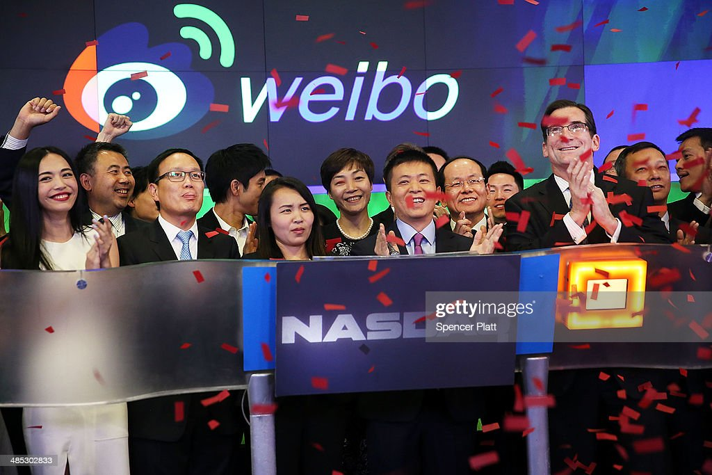 China's Weibo CEO Charles Chao (center) stands with Robert Greifeld, Nasdaq CEO, moments after Weibo began trading on the Nasdaq exchange under the ticker symbol WB on April 17, 2014 in New York City. Weibo Corp, a Twitter-like messaging service company, priced its initial public offering (IPO) at $17 per American Depository Share (ADS).