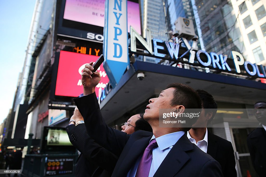 China's Weibo CEO Charles Chao takes a cell phone picture in Times Square moments after Weibo began trading on the Nasdaq exchange under the ticker symbol WB on April 17, 2014 in New York City. Weibo Corp, a Twitter-like messaging service company, priced its initial public offering (IPO) at $17 per American Depository Share (ADS).