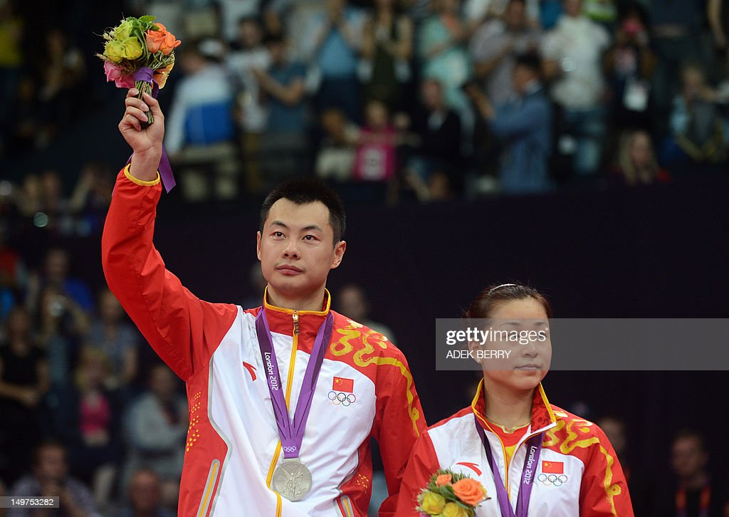 China's Xu Chen (L) and Ma Jin acknowledge the crowds applause after winning the silver medal during the Mixed Doubles gold medal match at the London 2012 Olympic Games in London, on August 3, 2012. AFP PHOTO / ADEK BERRY
