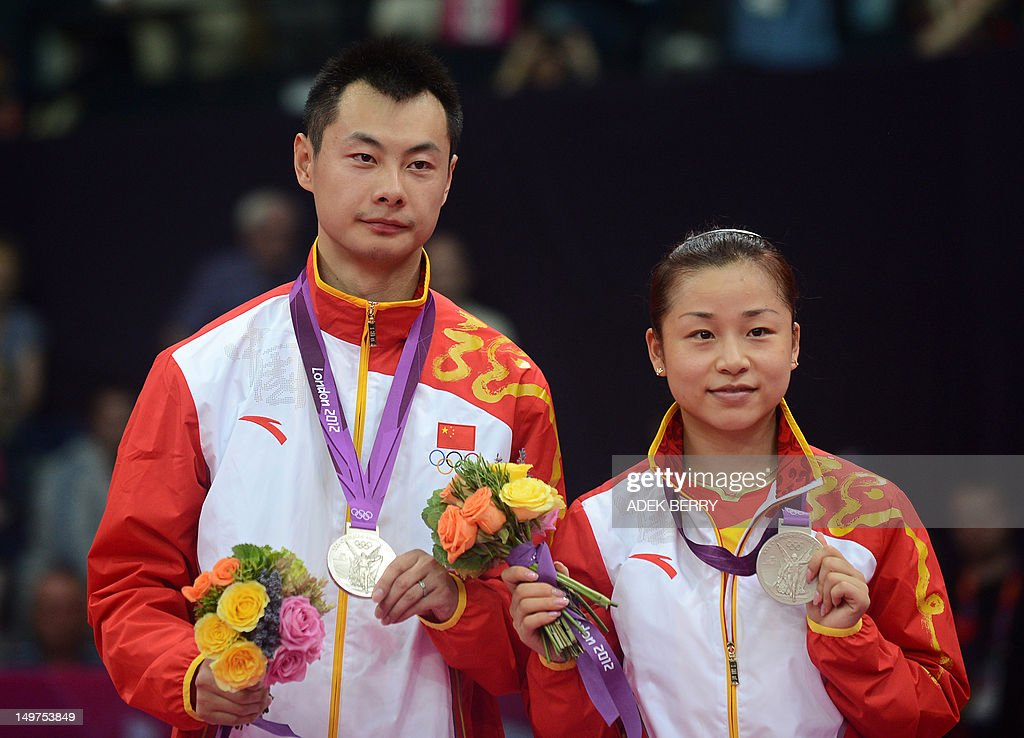 China's Xu Chen (L) and Ma Jin pose with their silver medals after the Mixed Doubles gold medal match at the London 2012 Olympic Games in London, on August 3, 2012. AFP PHOTO / ADEK BERRY