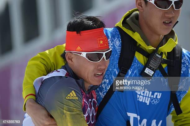 China's Xu Wenlong is helped by a team official after finishing last the Men's CrossCountry Skiing 50km Mass Start Free at the Laura CrossCountry Ski...