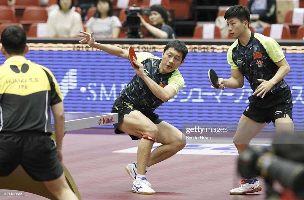 China's <a gi-track='captionPersonalityLinkClicked' href=/galleries/search?phrase=Xu+Xin+-+Table+Tennis+Player&family=editorial&specificpeople=15781496 ng-click='$event.stopPropagation()'>Xu Xin</a> (C) hits a shot as countryman Ma Long (R) looks on, during the men's doubles final of the International Table Tennis Federation (ITTF) World Tour Japan Open in Tokyo on June 19, 2016. They defeated the Taiwanese pair of Chuang Chih-yuan and Huang Sheng-sheng 3-0 to secure the title.