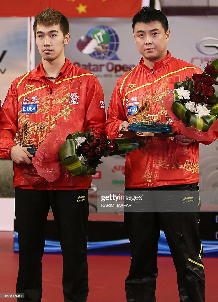 China's Yan An (L) and Wang Hao hold their trophies after winning the men's doubles final table tennis match at the ITTF Pro Tour Qatar Open in the Qatari capital Doha on February 24, 2013. AFP PHOTO / AL-WATAN DOHA / KARIM JAAFAR == QATAR OUT ==
