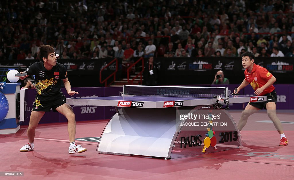 China's Yan An (L) serves to China's Wang Hao (R) on May 19, 2013 in Paris during their Men's quarter-final match of the World Table Tennis Championships.