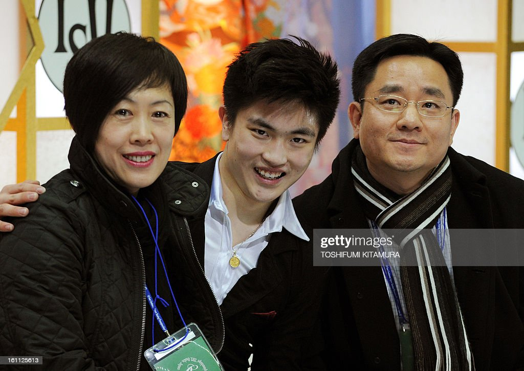 China's Yan Han (C) smiles with his coaches after his free skating performance in the men's event during the Four Continents figure skating championships in Osaka on February 9, 2013. AFP PHOTO / TOSHIFUMI KITAMURA