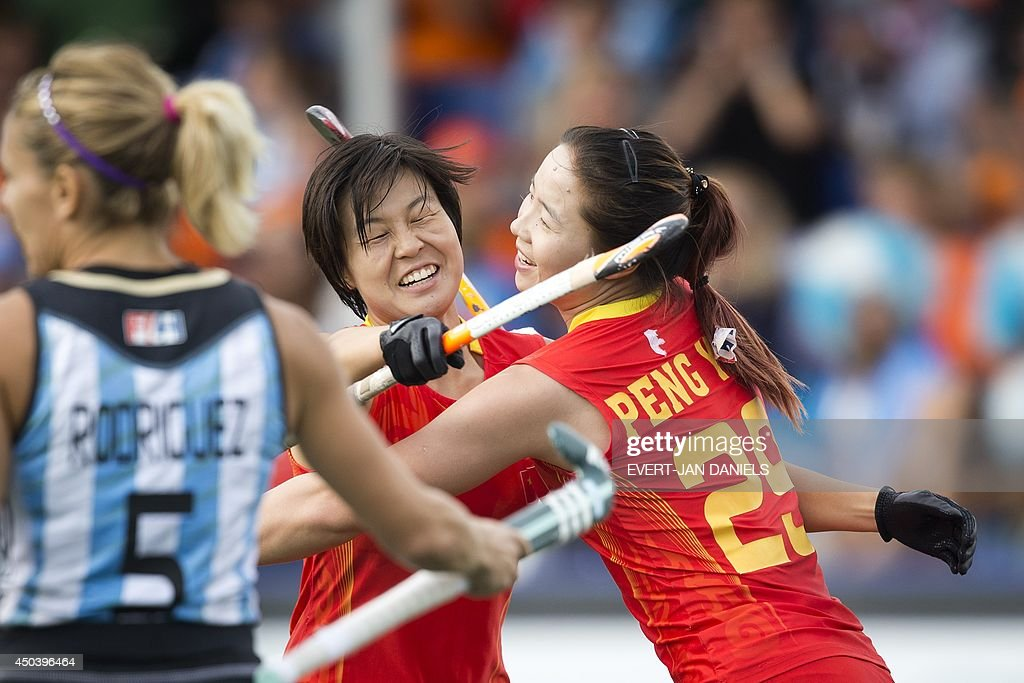 China's Yang Peng (R) celebrates her goal with China's Xiaoxu Xu (C) during the stage group match between Argentina and China of the women's tournament of the 2014 Field Hockey World Cup in The Hague, on June 10, 2014.