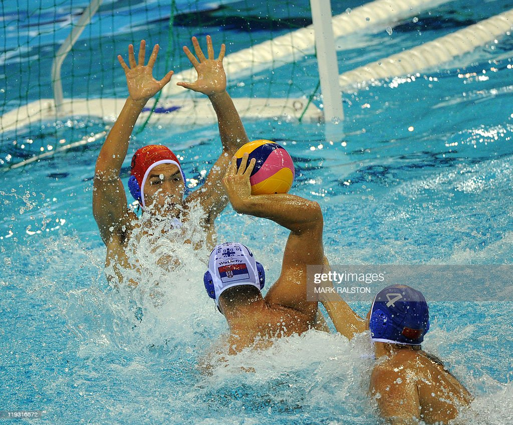 China's Yu Lijun and goalkeeper Ge Weiqing try to stop Serbia's Vanja Udovicic from scoring during their men's group B water polo preliminary round...