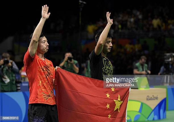 China's Zhang Jike and compatriot Ma Long hold the Chinese flag after the final men's singles table tennis matches at the Riocentro venue during the...