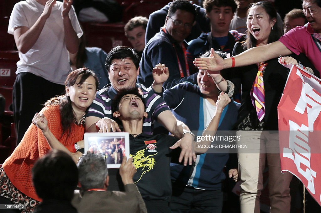China's Zhang Jike (C) celebrates with people in the stands, on May 20, 2013 in Paris, after his victory over China's Wang Hao in the Final of the Men's Singles of the World Table Tennis Championships. APF PHOTO/JACQUES DEMARTHON
