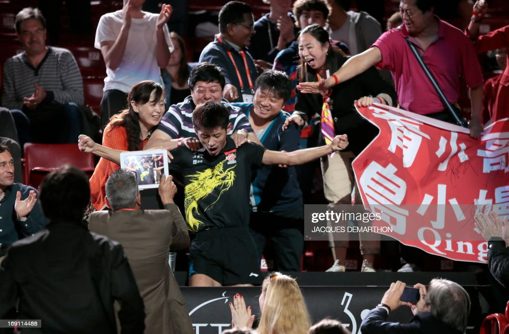 China's Zhang Jike (C) celebrates with people in the stands, on May 20, 2013 in Paris, after his victory over China's Wang Hao in the Final of the Men's Singles of the World Table Tennis Championships. APF