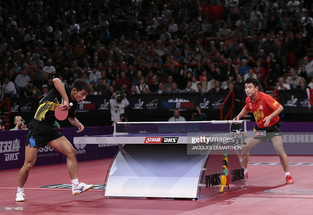 China's Zhang Jike (L) serves to China's Wang Hao (L) on May 20, 2013 in Paris, during the Final of the Men's Singles at the World Table Tennis Championships. Reigning champion Zhang Jike won the final (4-2). AFP PHOTO/JACQUES DEMARTHON