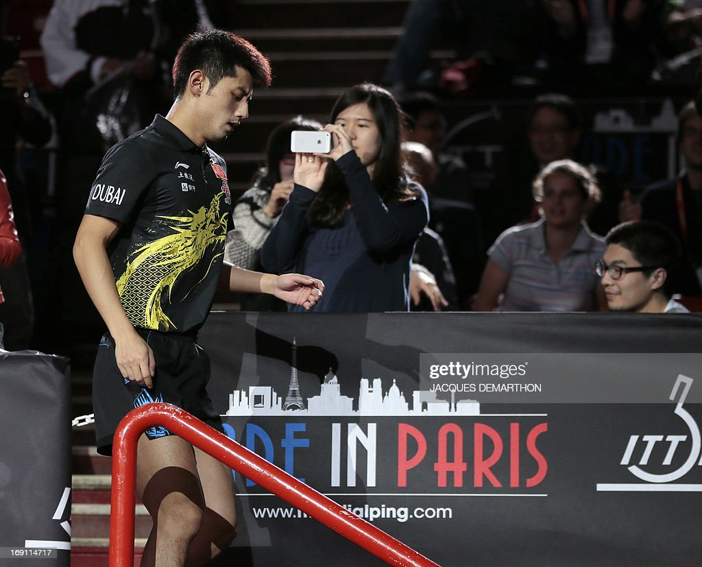 China's Zhang Jike walks back to the arena after he celebrated his victory over China's Wang Hao with relatives in the stands on May 20, 2013 in Paris, during the Final of the Men's Singles at the World Table Tennis Championships.