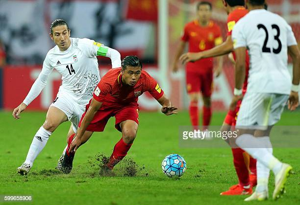 China's Zhang Yuning runs with the ball next to Iran's Andranik Teymourian during their 2018 World Cup qualifying football match in Shenyang...