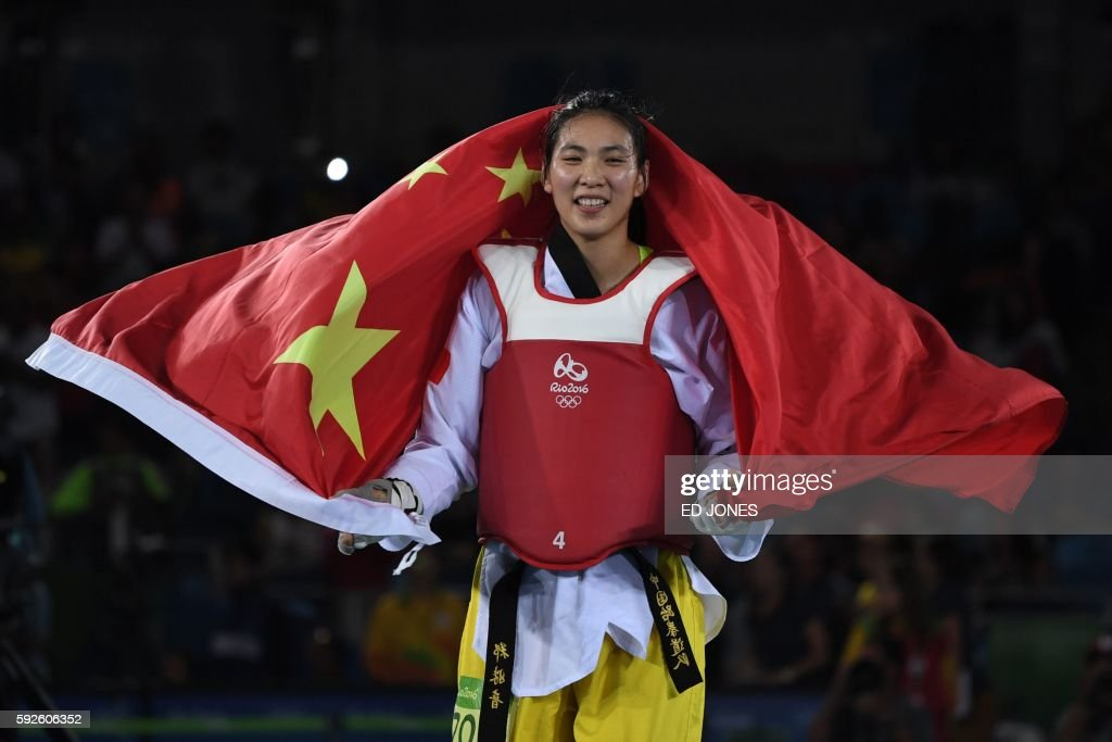 China's Zheng Shuyin celebrates after winning the womens taekwondo gold medal bout in the 67kg category as part of the Rio 2016 Olympic Games on...