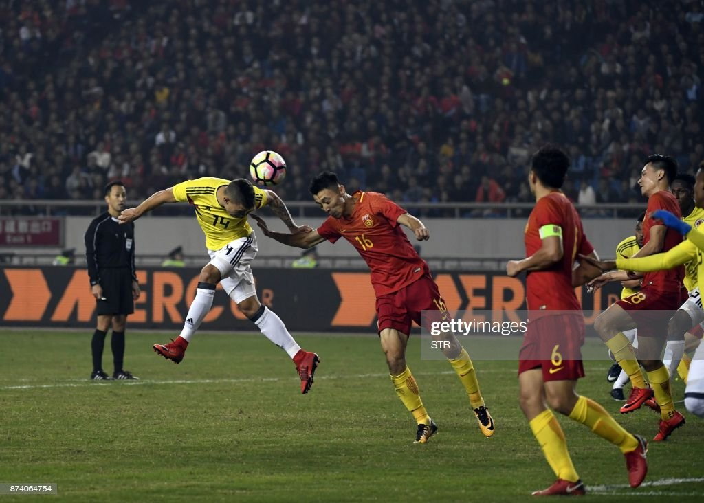 China's Zheng Zheng (3rd L) heads the ball next to Colombia's Andres Uribe (2nd L) during their international friendly football match in Chongqing, southwest China on November 14, 2017. A Colombia side missing James Rodriguez punished China 4-0 away in a friendly on November 14 as coach Jose Pekerman made wholesale changes from the team defeated in acrimony in South Korea. / AFP PHOTO / STR / China OUT