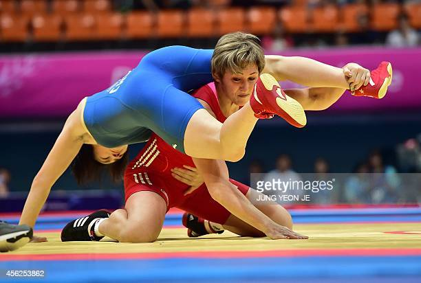 China's Zhou Feng competes with Kazakhstan's Guzel Manyurova in the women's freestyle 75 kg wrestling event for the gold medal during the 2014 Asian...