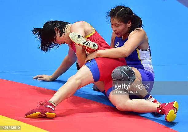 China's Zhou Feng competes with Mongolia's Burmaa Ochirbat in the women's freestyle 75 kg semifinal wrestling match during the 2014 Asian Games at...