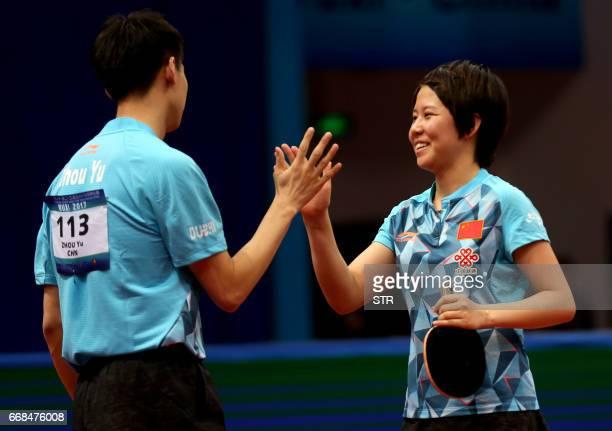 China's Zhou Yu and Chen Xingtong celebrate after winning the mixed doubles final match against Japan's Ito Mima and Morizono Masataka at the Asian...