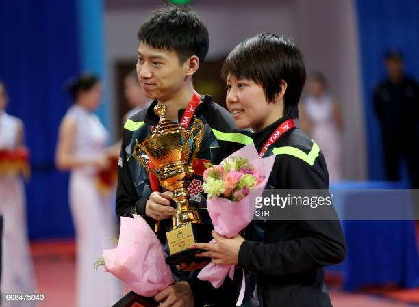 China's Zhou Yu and Chen Xingtong pose with their trophy after winning the mixed doubles final match against Japan's Ito Mima and Morizono Masataka...