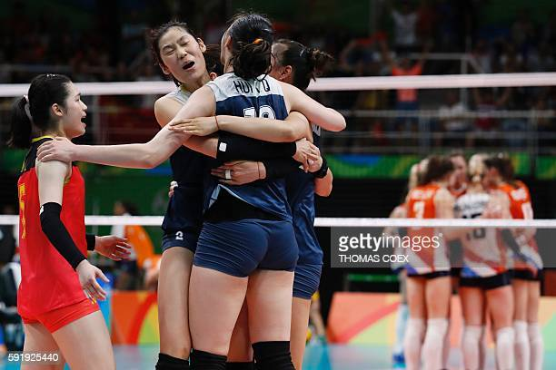 China's Zhu Ting and teammates celebrate after scoring during the women's semifinal volleyball match between China and the Netherlands at...