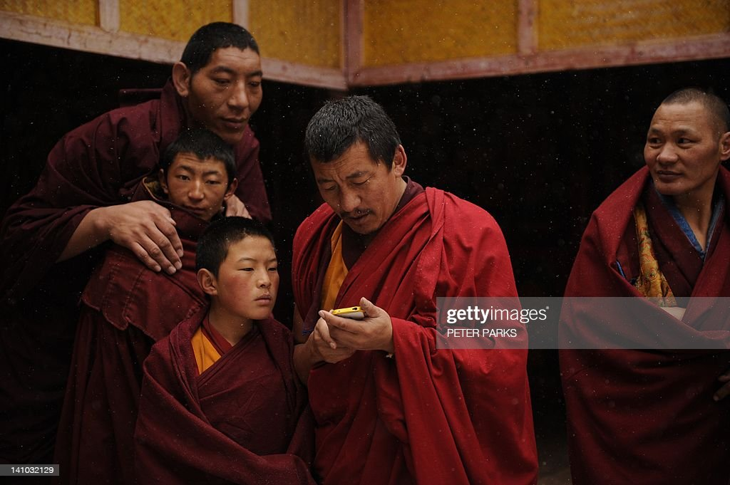 China-Tibet-unrest-religion,FOCUS by Robert Saiget A 2.14 metre Mongolian monk (Top-L) looks at a Tibetan monks iphone pictures with his fellow Tibetan monks after taking part in a ceremony at Lajia Monestry in China's northwest Qinghai province on March 9, 2012. As the anniversary of the Dalai Lama's flight into exile, March 10 has traditionally been a flashpoint for unrest in China's vast Tibetan-inhabited regions. AFP PHOTO/Peter PARKS