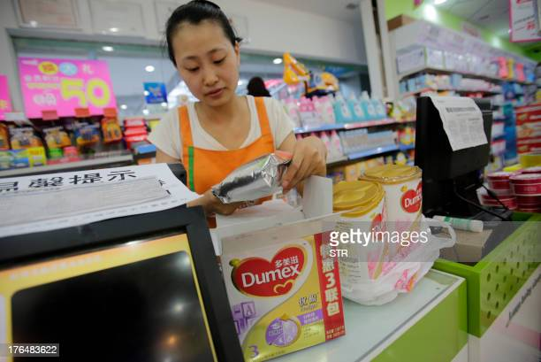 ChinatradepharmafoodmilkANALYSIS by Julien Girault This picture taken on August 7 2013 shows a sales clerk checking on returned Dumex baby formula...