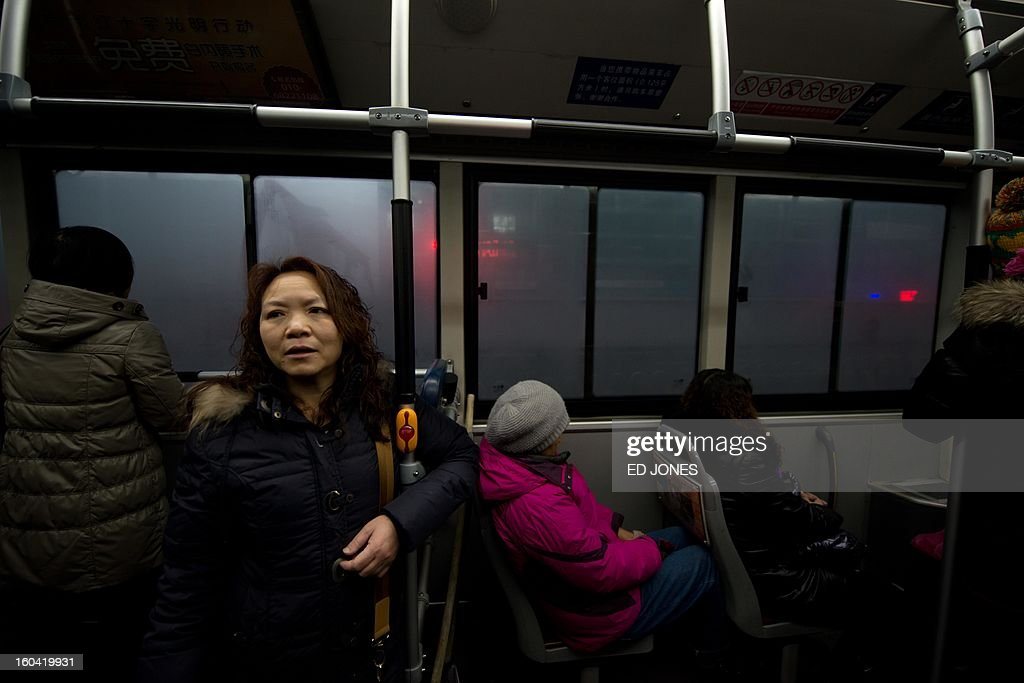 China-transport-migration,FEATURE by Neil Connor Domestic worker Chen Guolan stands in a bus after leaving the apartment of her employers, where she also lives, in Beijing on January 31, 2013 to catch a train bound for the south-western Chinese city of Chongqing, a journey of 32 hours, and where she will also take another train for a further 6 hours to reach her home in Yiban, Sichuan province. The world's largest annual migration is underway in China with tens of thousands in the capital boarding trains to journey home for Lunar New Year celebrations. Passengers will log 220 million train rides during the 40-day travel season as they criss-cross the country to celebrate with their families on February 10, but just as making the trip home can be laborious -- often lasting one or two days -- so can simply acquiring a seat on the train, and every year complaints arise about the inefficiency or unfairness of the system, although an initiative allowing travelers to purchase tickets online aims to curb long queuing times. AFP PHOTO / Ed Jones