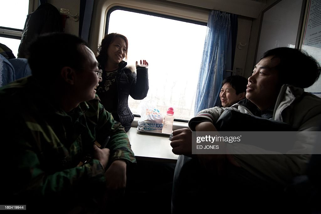 China-transport-migration,FEATURE by Neil Connor Domestic worker Chen Guolan (back L) talks with fellow passengers as she sits on a train leaving the Beijing West Railway Station for the south-western Chinese city of Chongqing, a journey of 32 hours, and where she will also take another train for a further 6 hours to reach her home in Yiban, Sichuan province, early on January 31, 2013. The world's largest annual migration is underway in China with tens of thousands in the capital boarding trains to journey home for Lunar New Year celebrations. Passengers will log 220 million train rides during the 40-day travel season as they criss-cross the country to celebrate with their families on February 10, but just as making the trip home can be laborious -- often lasting one or two days -- so can simply acquiring a seat on the train, and every year complaints arise about the inefficiency or unfairness of the system, although an initiative allowing travelers to purchase tickets online aims to curb long queuing times. AFP PHOTO / Ed Jones