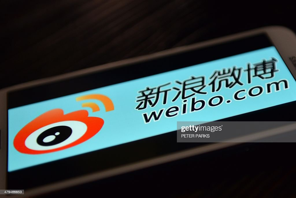 China-US-Internet-listing-politics,FOCUS by Bill SAVADOVE This photo illustration taken on March 19, 2014 shows the logo of Chinese microblogging platform Weibo on a smartphone in the Chinese financial city of Shanghai. While Internet giants like Twitter and Google champion free speech, the US listing document for Chinese microblogging platform Weibo is littered with 56 pages of warnings on the risks of operating in a country which seeks to control information. AFP PHOTO/Peter PARKS