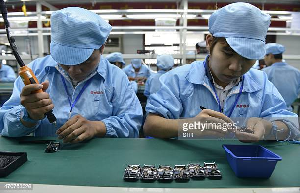 ChinaUSITInternetlifestyleAppleFOCUS by Tom Hancock This picture taken on April 22 2015 shows Chinese workers assembling a cheaper local alternative...