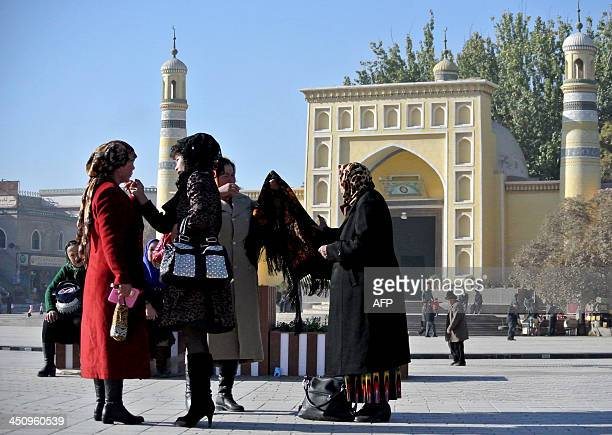 ChinaXinjiangunrestsocialFEATURE by Carol Huang This picture taken on November 8 2013 shows a group of Uighur women outside a mosque in Kashgar...