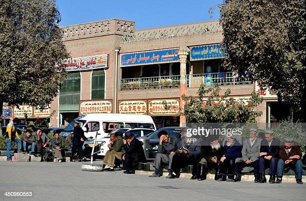 ChinaXinjiangunrestsocialFEATURE by Carol Huang This picture taken on November 8 2013 shows a group of Uighur men sitting by a street in Kashgar...