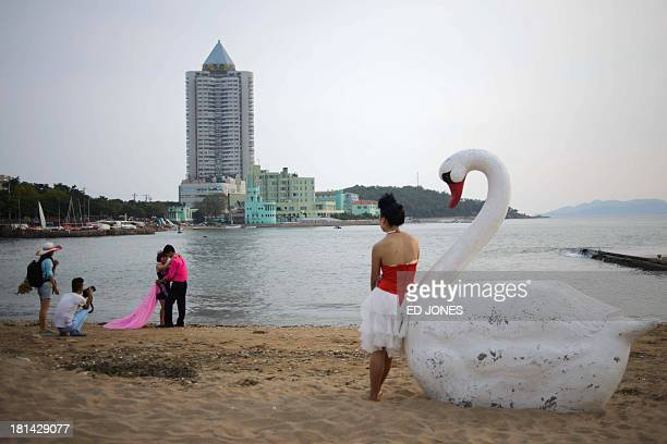 A Chinease couple have their wedding photos taken on a beach in Qingdao Shandong province on September 21 2013 The eastern Chinese port city is home...