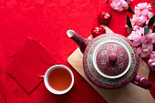 Chines new year Celebration background with cup of tea and teapot on red background, top view.