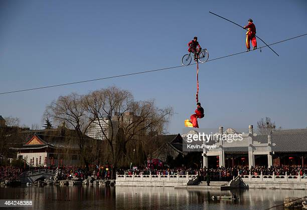 Chinese acrobats balance on a high wire as they perform during Spring Festival celebrations at a Temple Fair on February 22 2015 in Beijing China The...