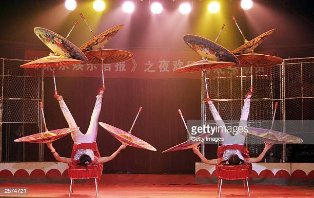 Chinese acrobats balance umbrellas during a performance by the national 'Star Circus' October 9 2003 in Beijing China The circus performs in Beijing...