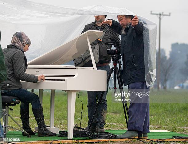 Chinese activist and artist Ai Weiwei holds a sheet of plastic covering Syrian pianist Nour Al Khzam as she plays the piano for the first time in...