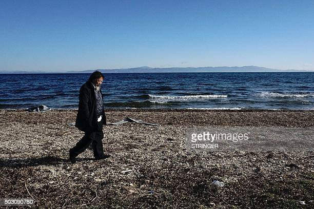 Chinese activist and artist Ai Weiwei walks on a beach near the town of Mytilene on the Greek island of Lesbos on January 1 2016 Ai Weiwei visits the...