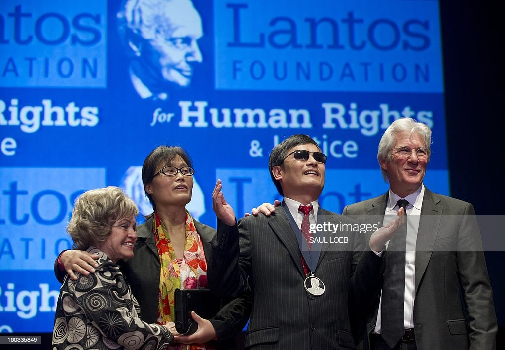 Chinese activist Chen Guangcheng (2nd R) raises his arms after being presented with the Tom Lantos Human Rights Prize alongside actor Richard Gere (R), Annette Lantos (L), wife of the late US Congressman Tom Lantos and Guangcheng's wife, Yuan Weijing (2nd L), during a ceremony at the US Capitol in Washington, DC, on January 29, 2013. The prize, awarded annually, honors Guangcheng for his work advocating on behalf of tens of thousands of Chinese fighting for human rights. AFP PHOTO / Saul LOEB