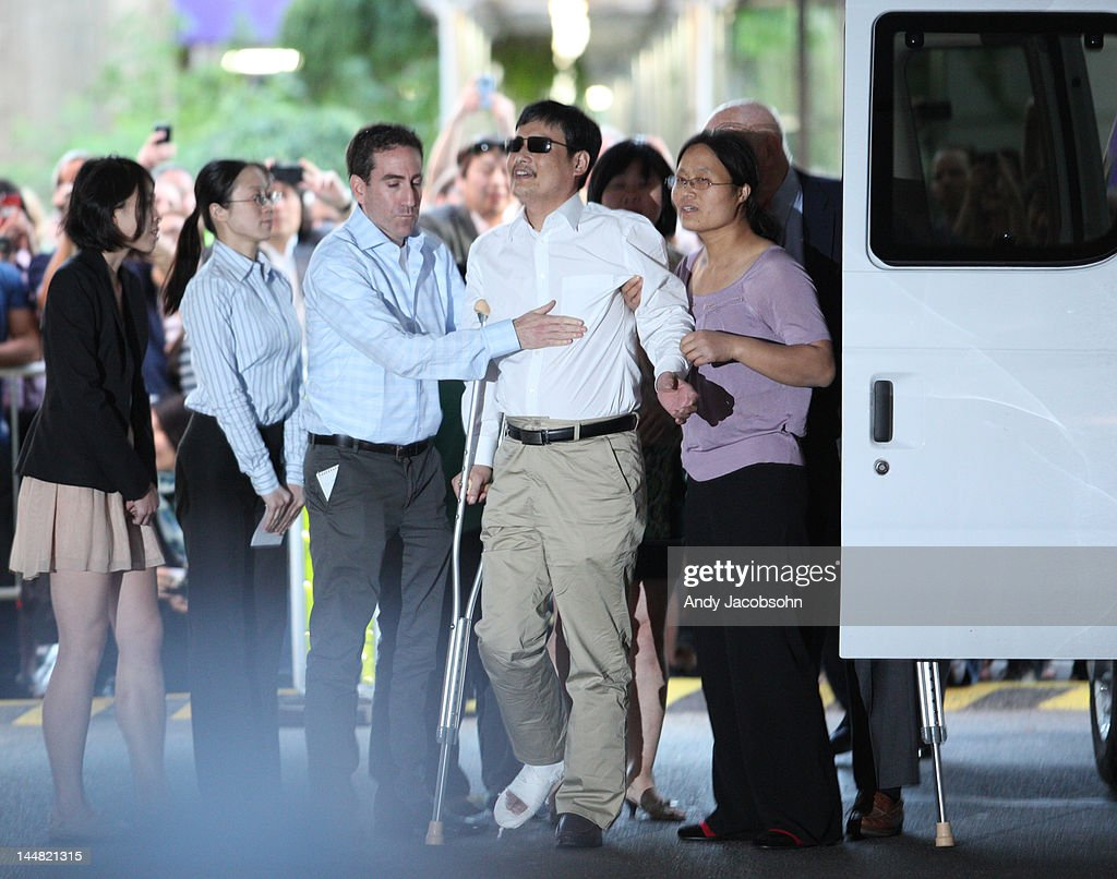 Chinese activist Chen Guangcheng steps out of a van with his wife Yuan Weijing beside him before making remarks to the media upon arriving on the...