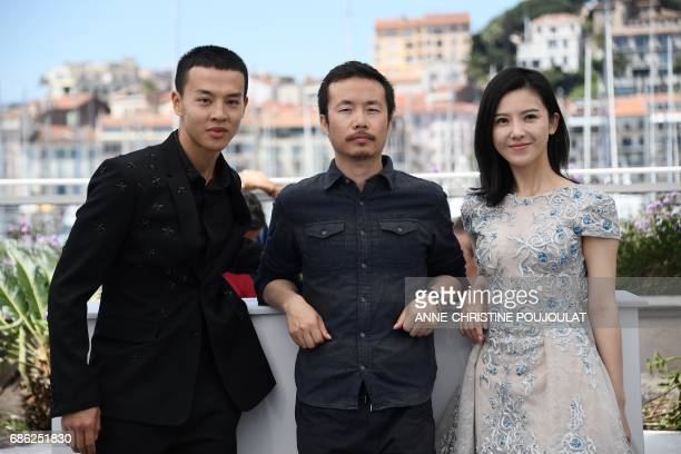 Chinese actor Yin Fang Chinese director Li Ruijun and Chinese actress Yang Zishan pose on May 21 2017 during a photocall for the film 'Walking past...