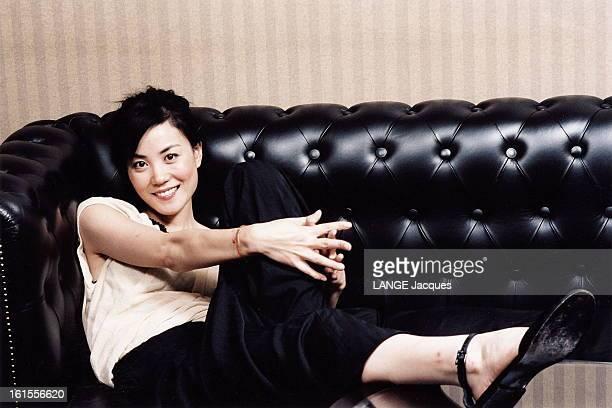 Chinese Actress Wang Fei Attitude souriante de WANG FEI installée sur un canapé dans un appartement