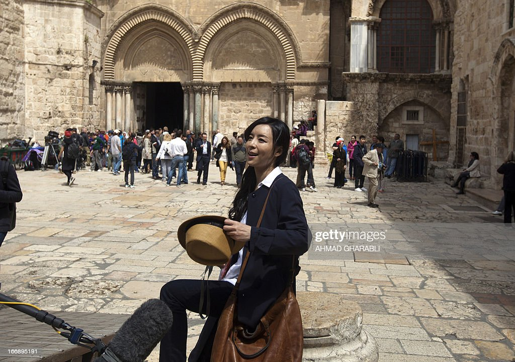 Chinese actress Zhang Jingchu (C) carries her hat during the filming of the movie 'Old Cinderella' outside the Church of the Holy Sepulcher in Jerusalem's Old City on April 18, 2013. A Chinese production company is shooting scenes of a movie directed by Lu Chuan, with the sponsorship of the Israeli Ministry of Tourism.