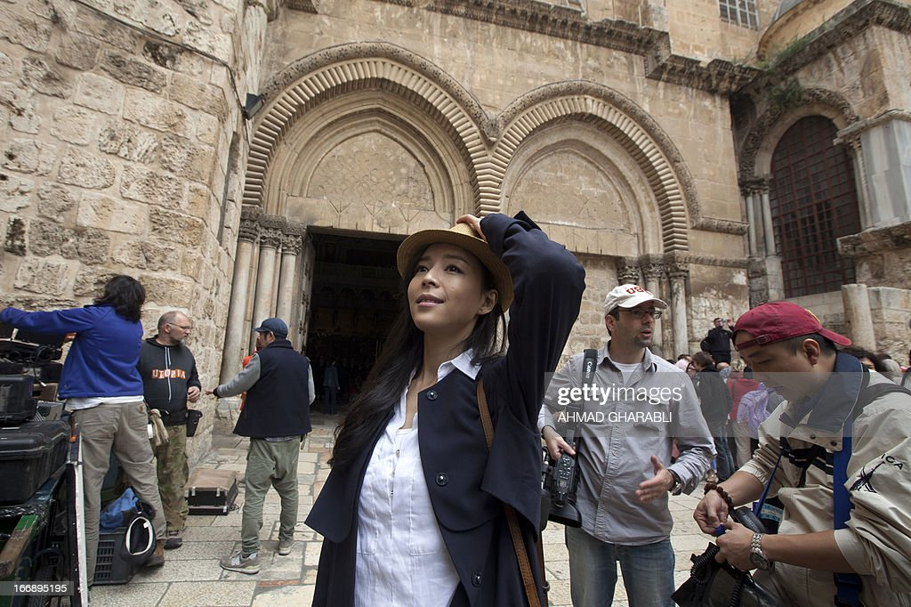 Chinese actress Zhang Jingchu (C) holds on to her hat during the filming of the movie 'Old Cinderella' outside the Church of the Holy Sepulcher in Jerusalem's Old City on April 18, 2013. A Chinese production company is shooting scenes of a movie directed by Lu Chuan, with the sponsorship of the Israeli Ministry of Tourism.
