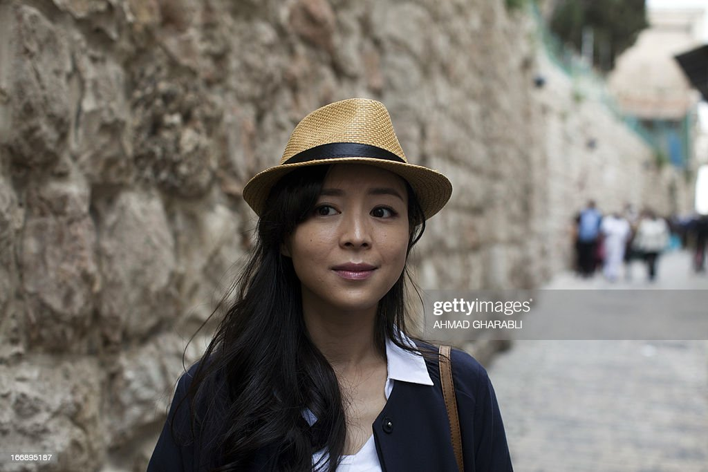 Chinese actress Zhang Jingchu (C) poses for a picture during the filming of the movie 'Old Cinderella' outside the Church of the Holy Sepulcher in Jerusalem's Old City on April 18, 2013. A Chinese production company is shooting scenes of a movie directed by Lu Chuan, with the sponsorship of the Israeli Ministry of Tourism.