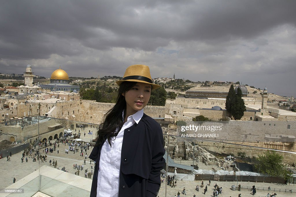 Chinese actress Zhang Jingchu poses for a picture with Jerusalem's al-Aqsa mosque compound in the background, during the filming of the movie 'Old Cinderella' outside the Church of the Holy Sepulcher in Jerusalem's Old City on April 18, 2013. A Chinese production company is shooting scenes of a movie directed by Lu Chuan, with the sponsorship of the Israeli Ministry of Tourism. AFP PHOTO/AHMAD GHARABLI