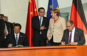Chinese Agriculture Minister Han Changfu and German Agriculture and Consumer Protection Minister Christian Schmidt sign a contract in front of Li...