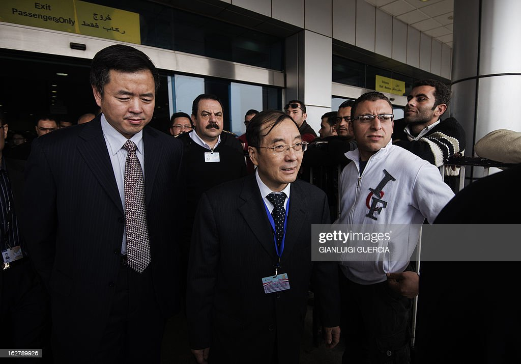 Chinese Ambassador to Egypt Song Aiguo (C) is escorted by an unidentified immigration official from Hong Kong (L) as they arrive at Cairo International Airport on February 27, 2013. Four investigating teams were formed after Egypt's Prime Minister Hisham Qandil ordered a probe into the hot air balloon crash on February 26, in the ancient temple city of Luxor, that killed tourists from Hong Kong, Japan, Britain, France and Hungary. AFP PHOTO/GIANLUIGI GUERCIA