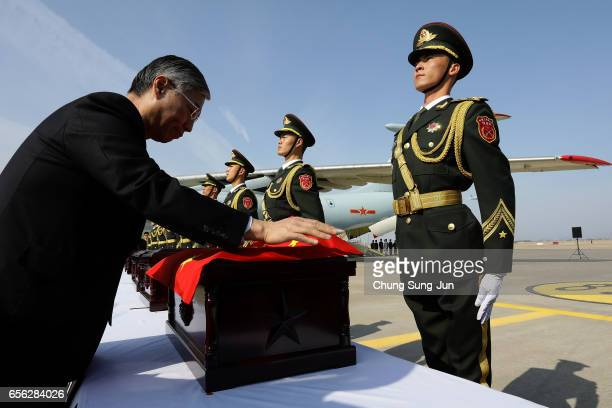 Chinese Ambassador to South Korea Qiu Guohong covers caskets containing the remains of Chinese soldiers with a Chinese national flag during the...